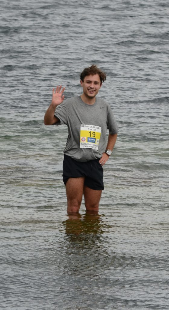 2nd placed Ewan Dudding cools off in the sea.