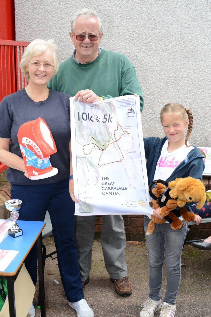 Rhona Elder, Aland Milstead and Morgan Faith, 9, on the CHEL stall hold a te towel map produced for this year's Carradale Canter. 25_c26primaryfun01