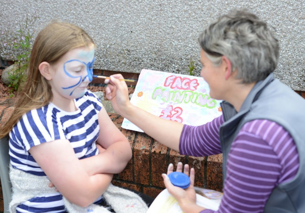 Emma Macalister Hall paints eight-year-old Abbie Erskine's face. 25_c26primaryfun02