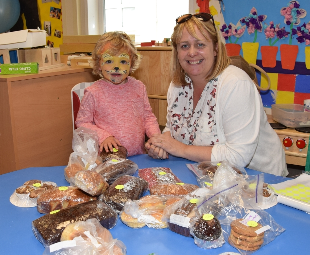 Little Denver the lion, three, helps Meadows Under Fives assistant manager Caroline Deans with the baking stall. 50_c31meadows03_baking stall