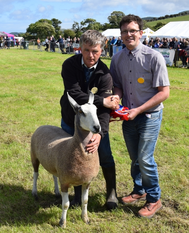 Kintyre Agricultural Society president James Young presents John McLachlan with the champion of champions rosette for his wife Jean's Bluefaced Leicester gimmer. 50_c32kintyreshow52_champion of champions