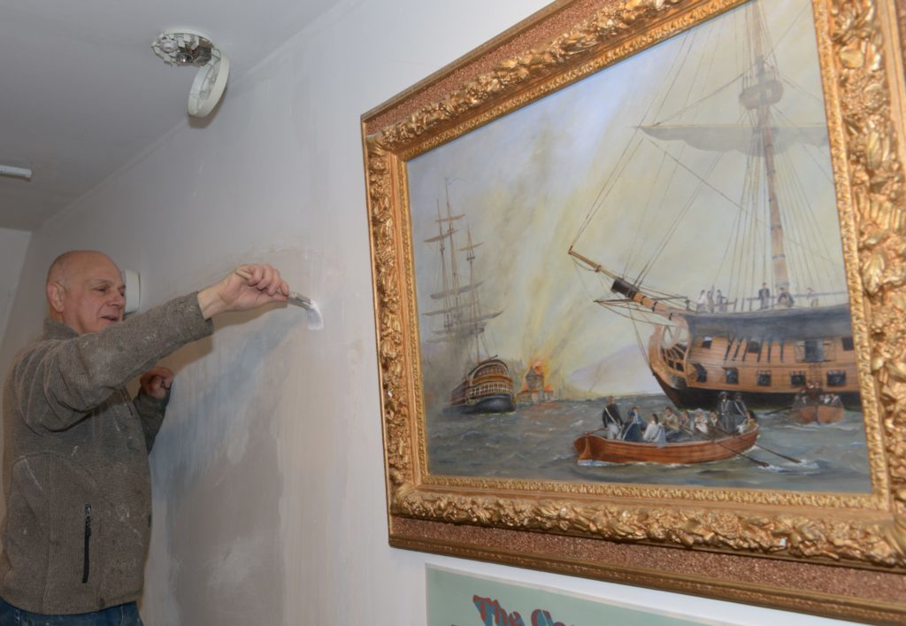 Decorator David Prag paints the back wall alongside an oil painting of a scene from East Kintyre's past. 25_c15museum03