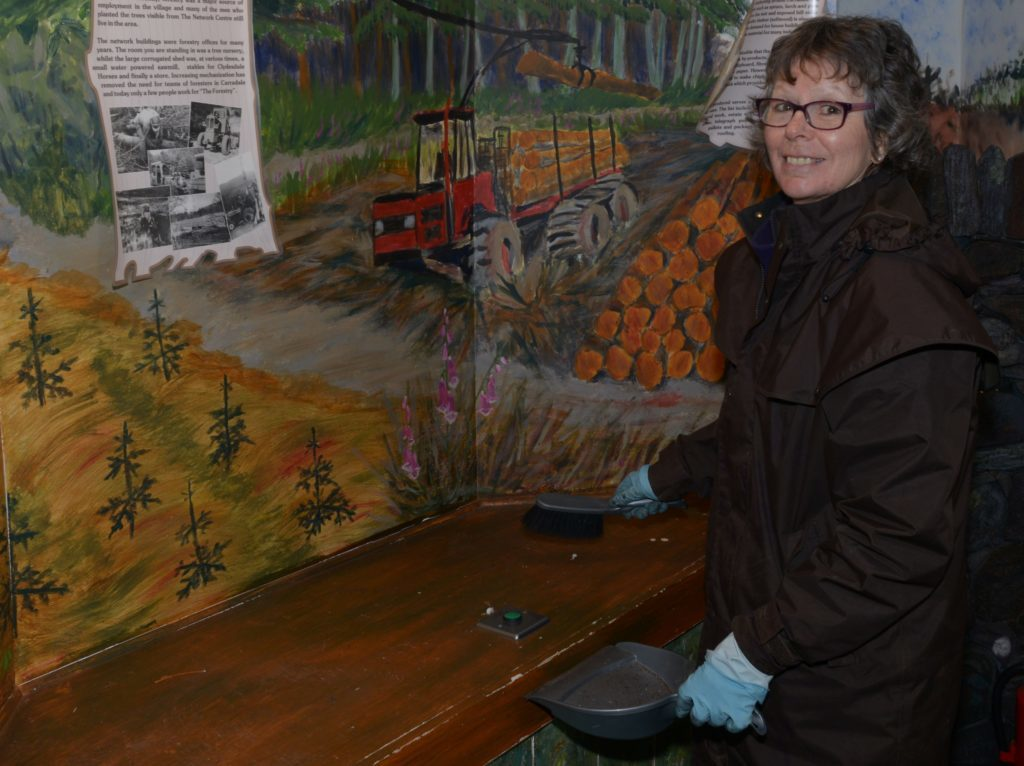 Lesley Prag sweeps a shelf. 25_c15museum05