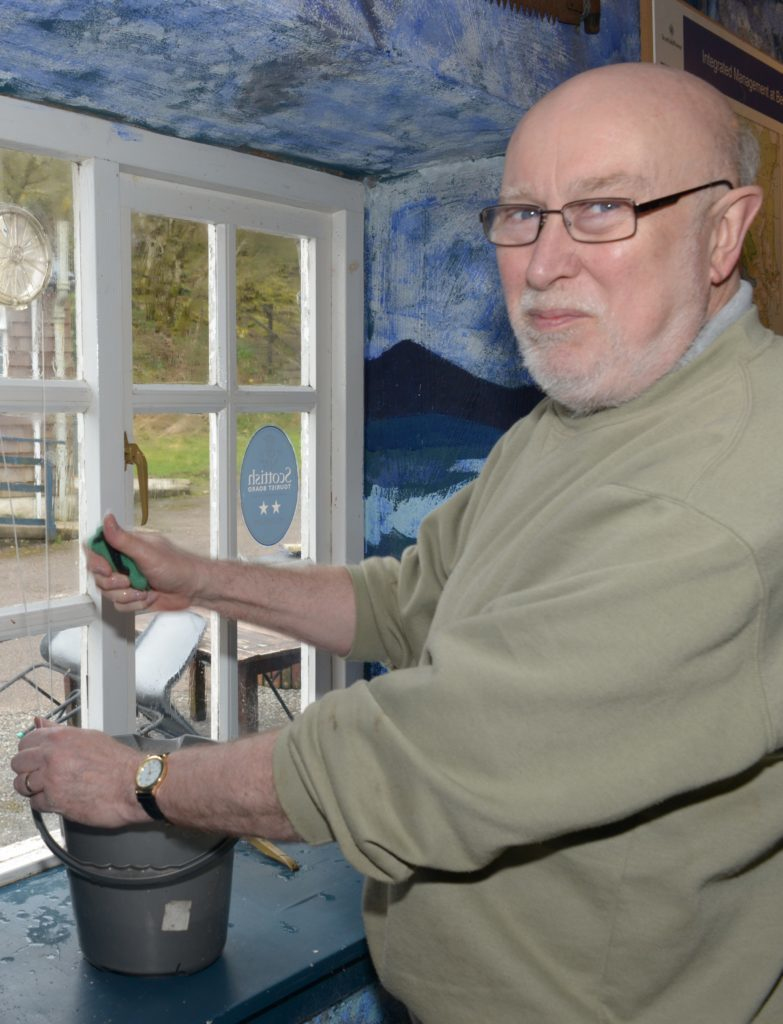 Bruce MacQuarrie cleans a window enclosure. 25_c15museum06