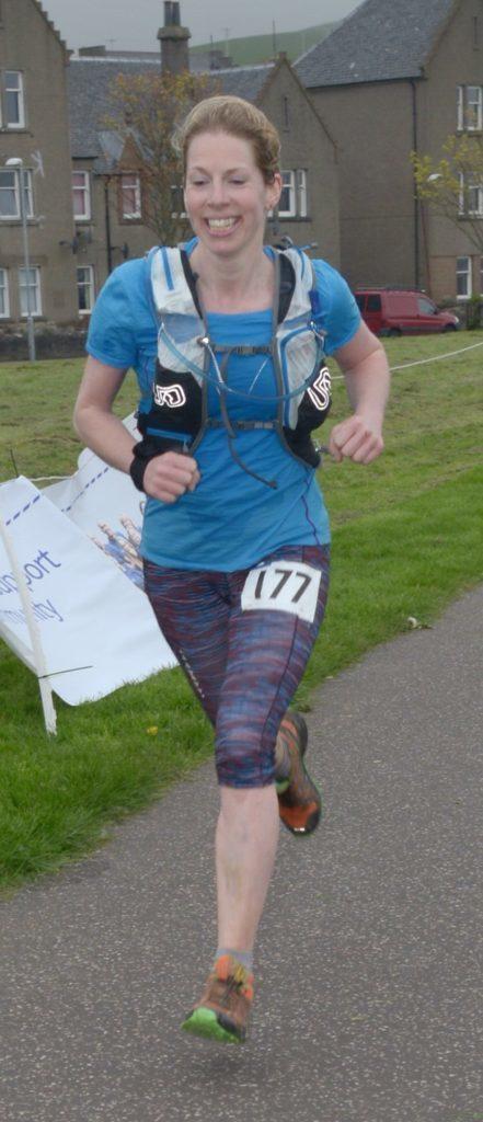 Women's winner Lucy Downie is all smiles as she crosses the ultra marathon line. 25_c19kwultra07_womens_winner