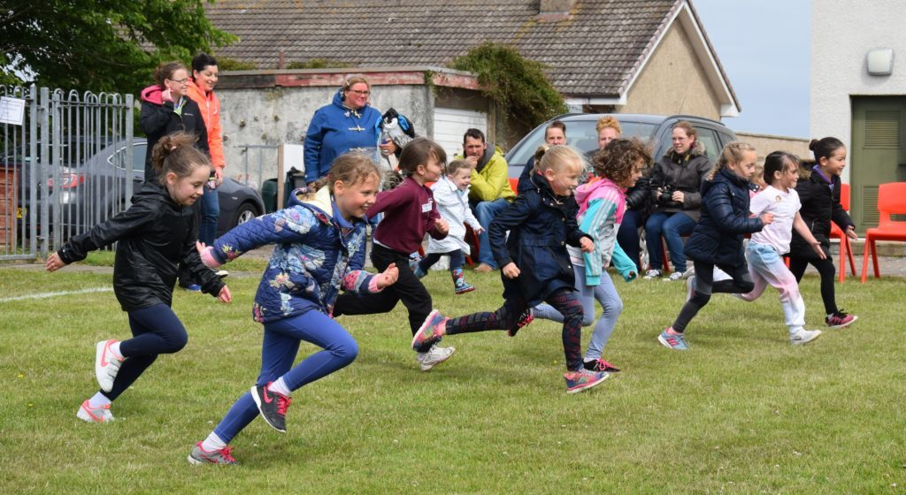 Junior girls grin as they compete in the flat race.
