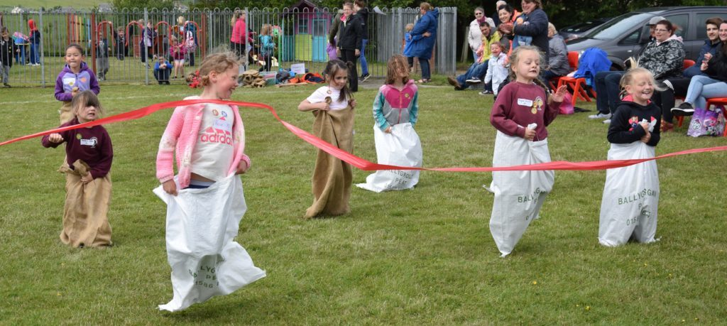 Girls grin as they reach the end of the sack race.