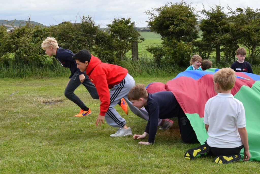 Boys race out of the parachute during the obstacle race.