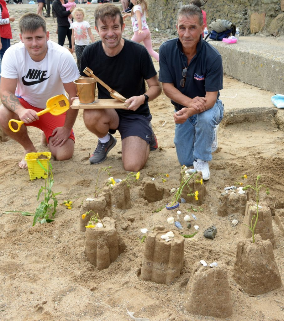 By the time judging was finished Finlay Blair had left the beach and from left: his dad Rhys Blair collected the prize from Jamie McIvor and Jamie McLean. 25_c32sandcastles02_RhysBlair_JamieMcIvor_JamieMcLean