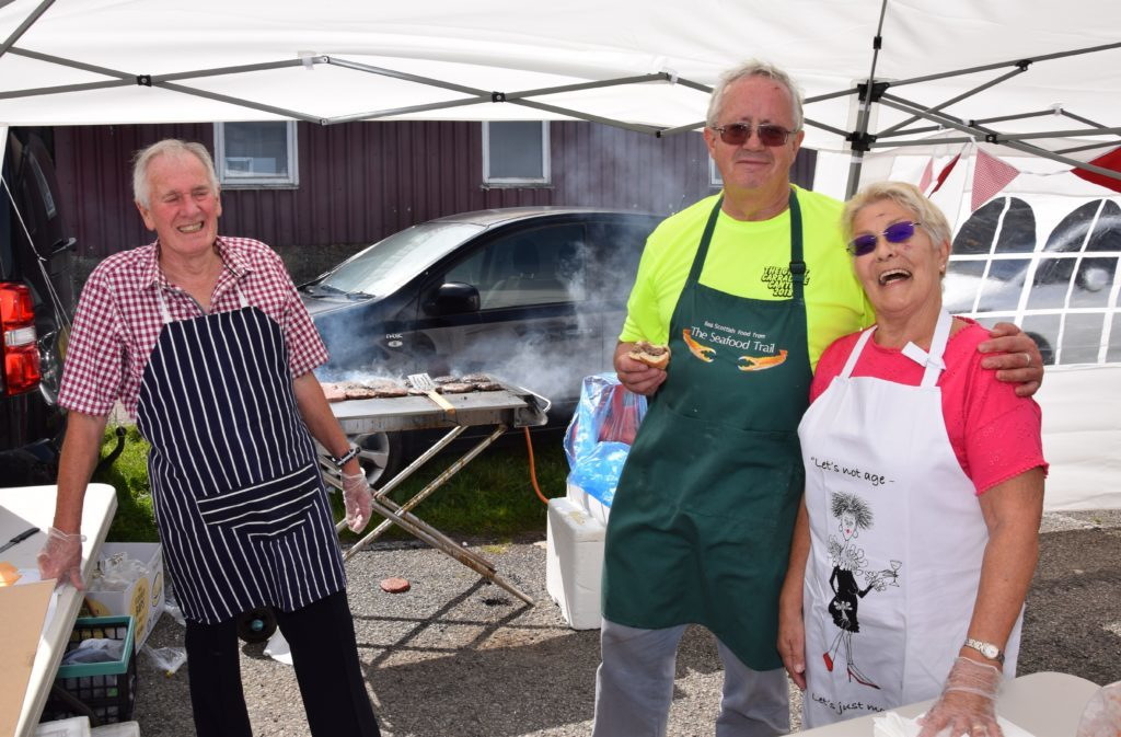 Alan Milstead, centre, chairman of CHEL, with Douglas and Margaret Brown who served up sizzling burgers.