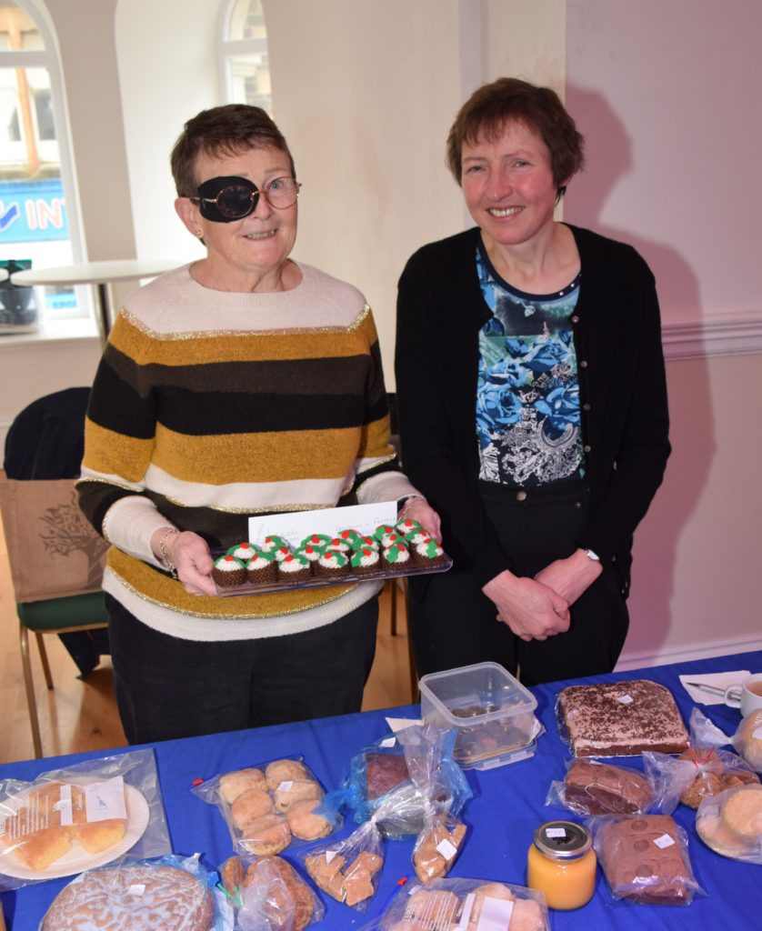 Dede Robertson holds her hand-knitted Christmas pudding treats, which she sold alongisde baking, with Margaret Littleson, right, at Cancer Research's coffee morning.