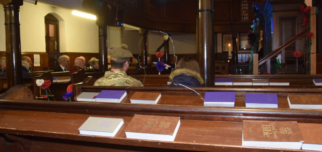 One of the transparent silhouettes representing the Great War's fallen sits in the pews behind Colour Sergeant Robbie Semple.
