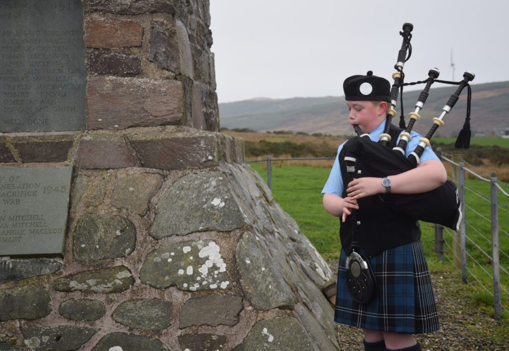 Calum O'Hanlon broke the two-minute silence with a poignant performance of The Battle's O'er.