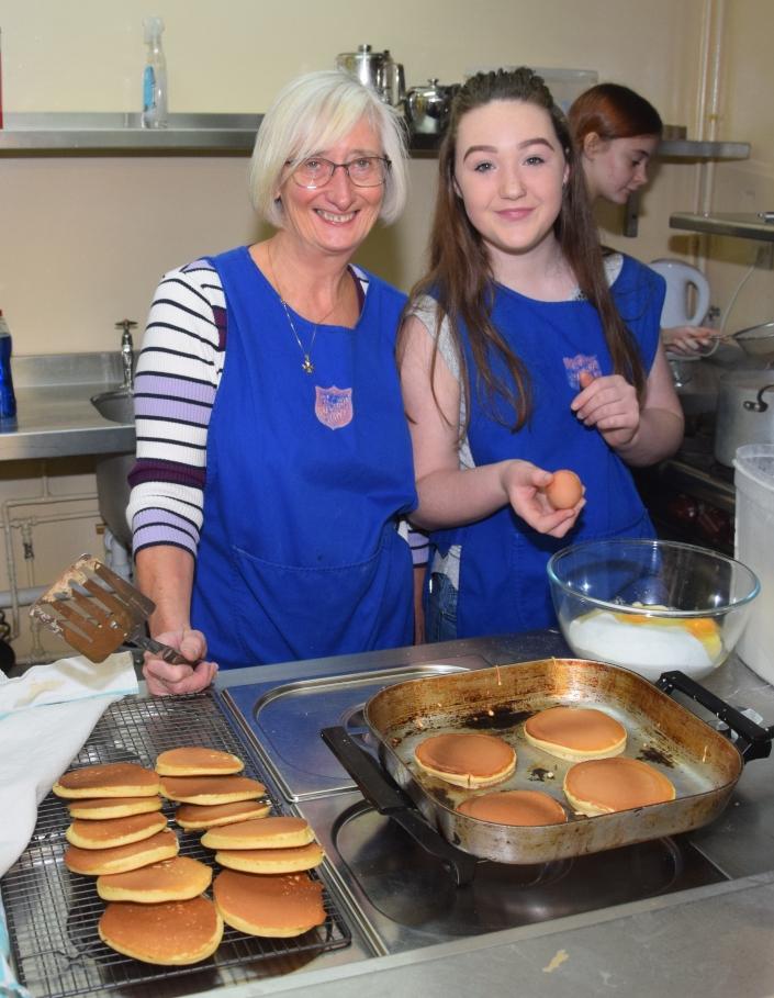 Margaret Raeside and Kelsey Graham prepare some pancakes.