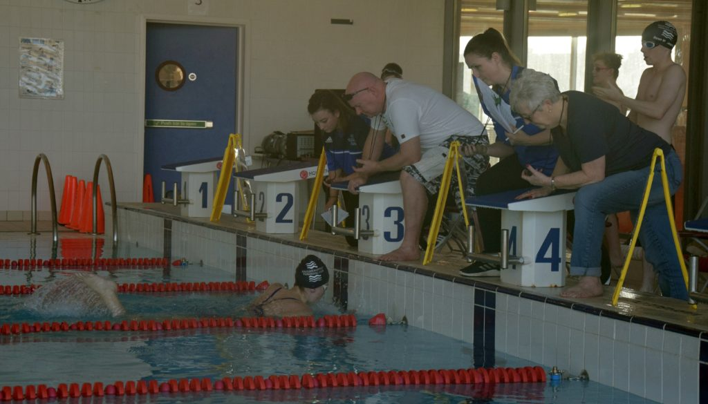 Organisers with stopwatches look on as Logan Colville finishes a race.
