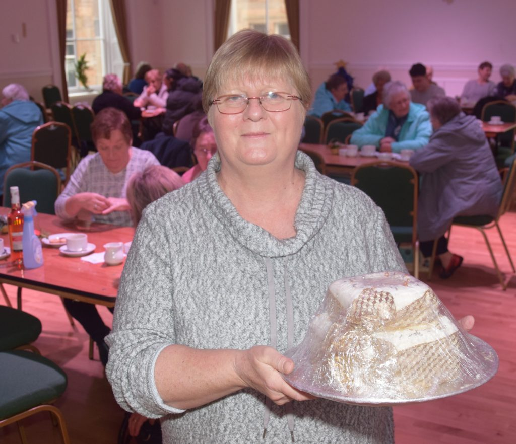 Sheena Robertson with the cake, donated by Frances Hill.