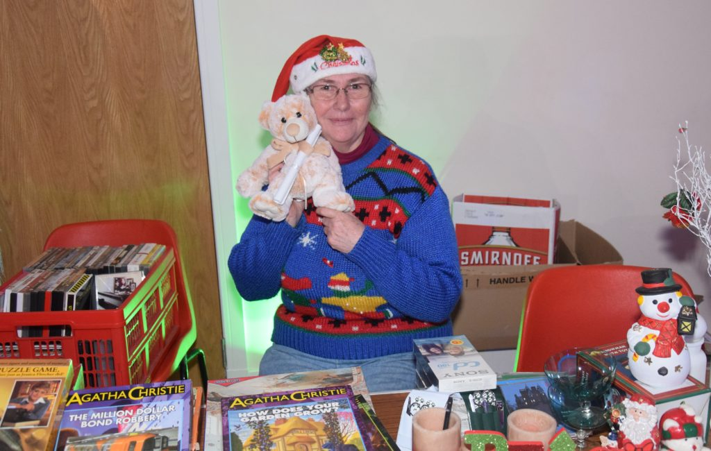Pat Wallace sells various items of bric-a-brac, including the cuddly teddy she is holding.
