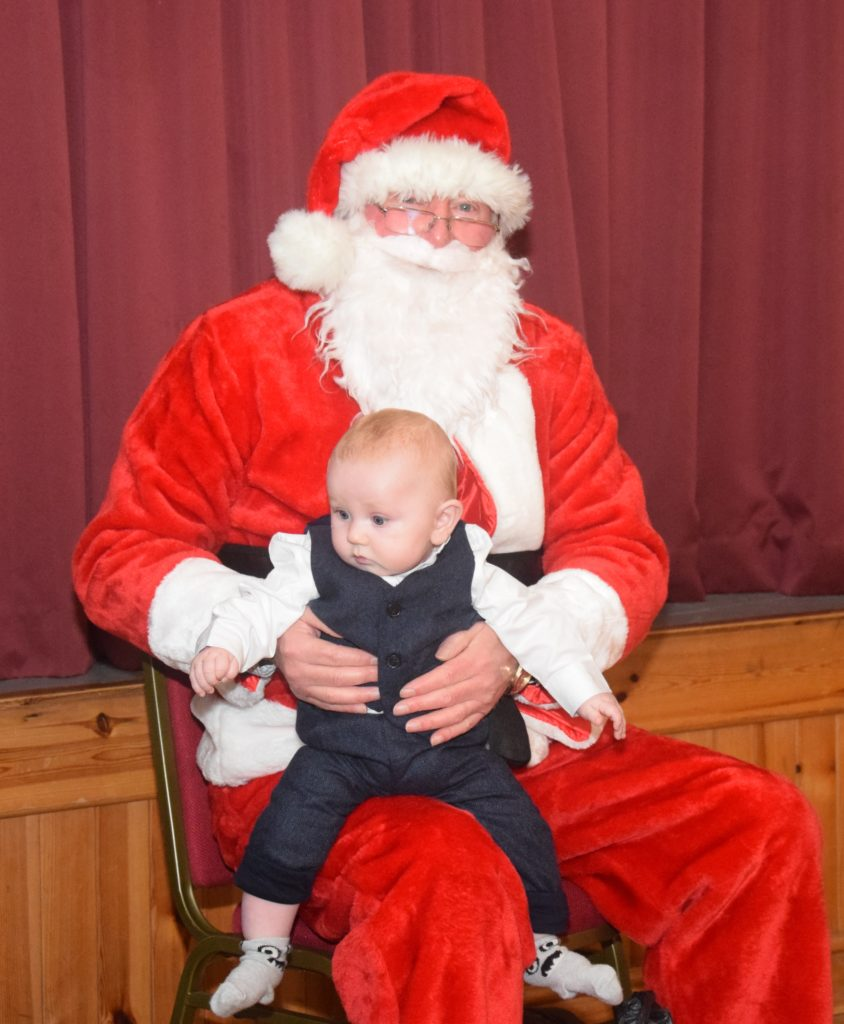 Seven-month-old Angus Hurd, one of the youngest party-goers, sits on Santa's lap.