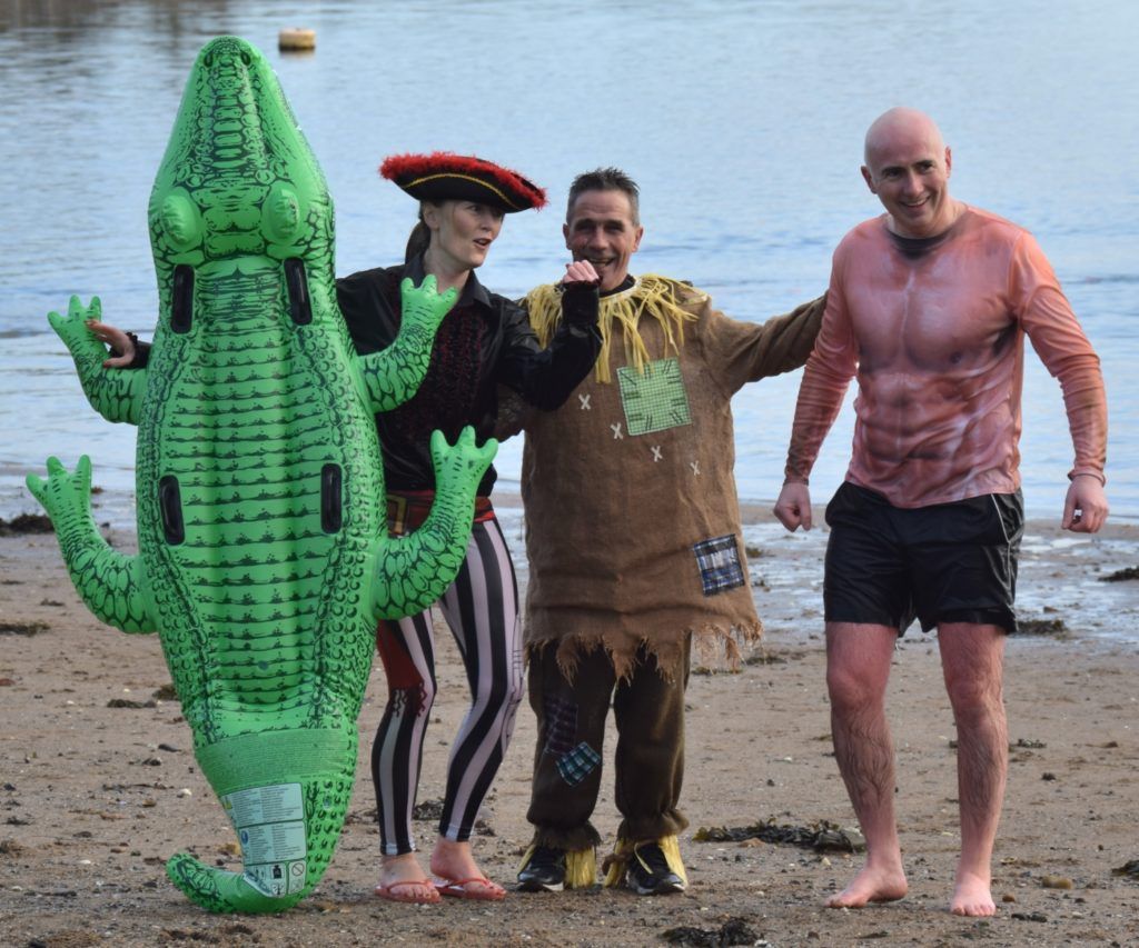Joanne Blair, Dalintober Beach Regeneration Group chairman Jamie McLean and Kenny Blair strike a pose after coming out of the water.