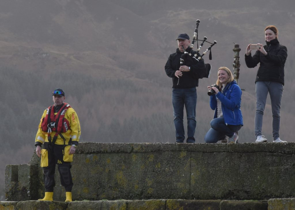 Piper Ian McKerral offered encouragement as safety officials stood by and spectators snapped photographs.