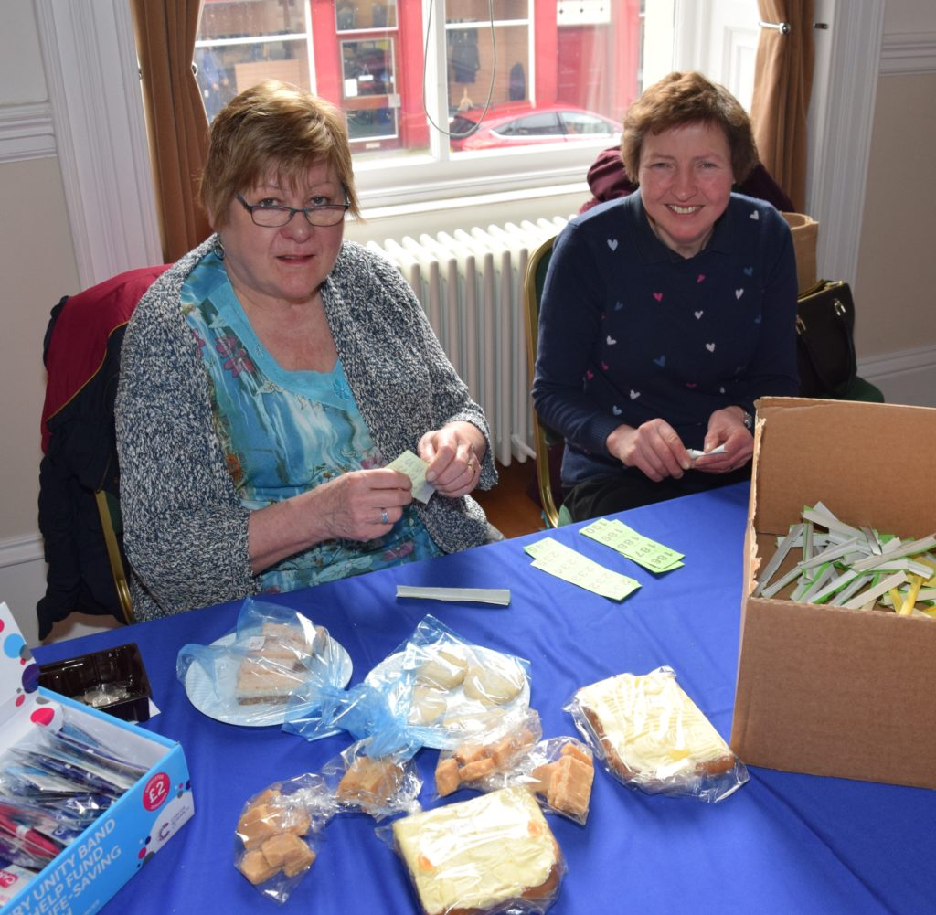 Elaine Hemmings and Margaret Littleson fold raffle tickets as they man the baking stall.