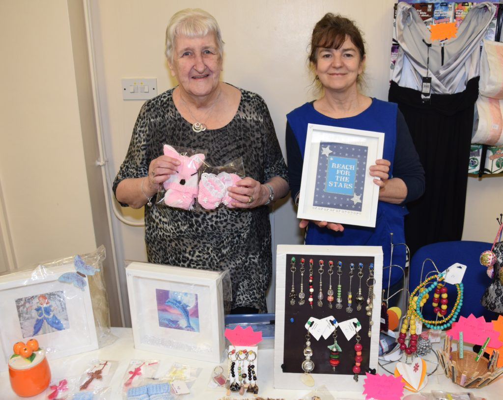 Myrtle Reid, left, holds knitting she created, while Michelle Plant holds a frame made at the church's craft group. All items were for sale on Saturday.
