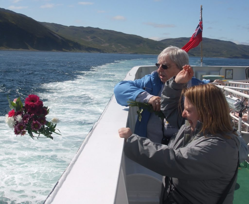 Ellen Sager and her daughter Andrea throw flowers off the Islay ferry in memory of Thomas Douglas.