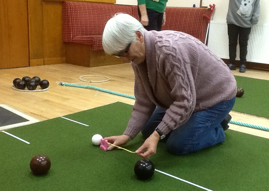 Umpire Kathleen McGougan measures the distance between bowls and the jack.