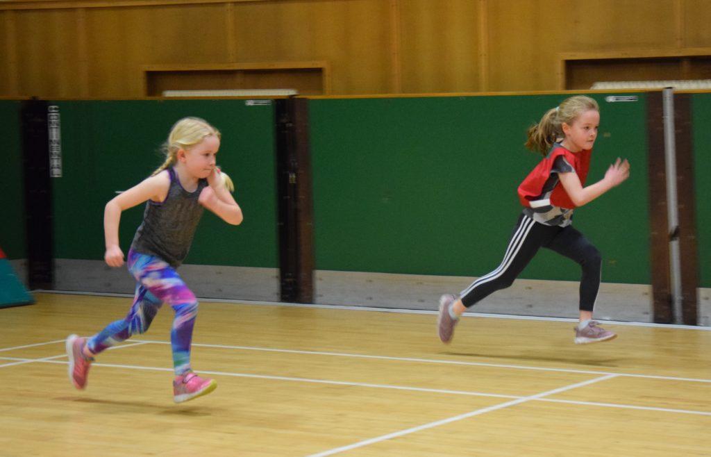 Amelie Ralston and Abigail McAllister race across the hall.