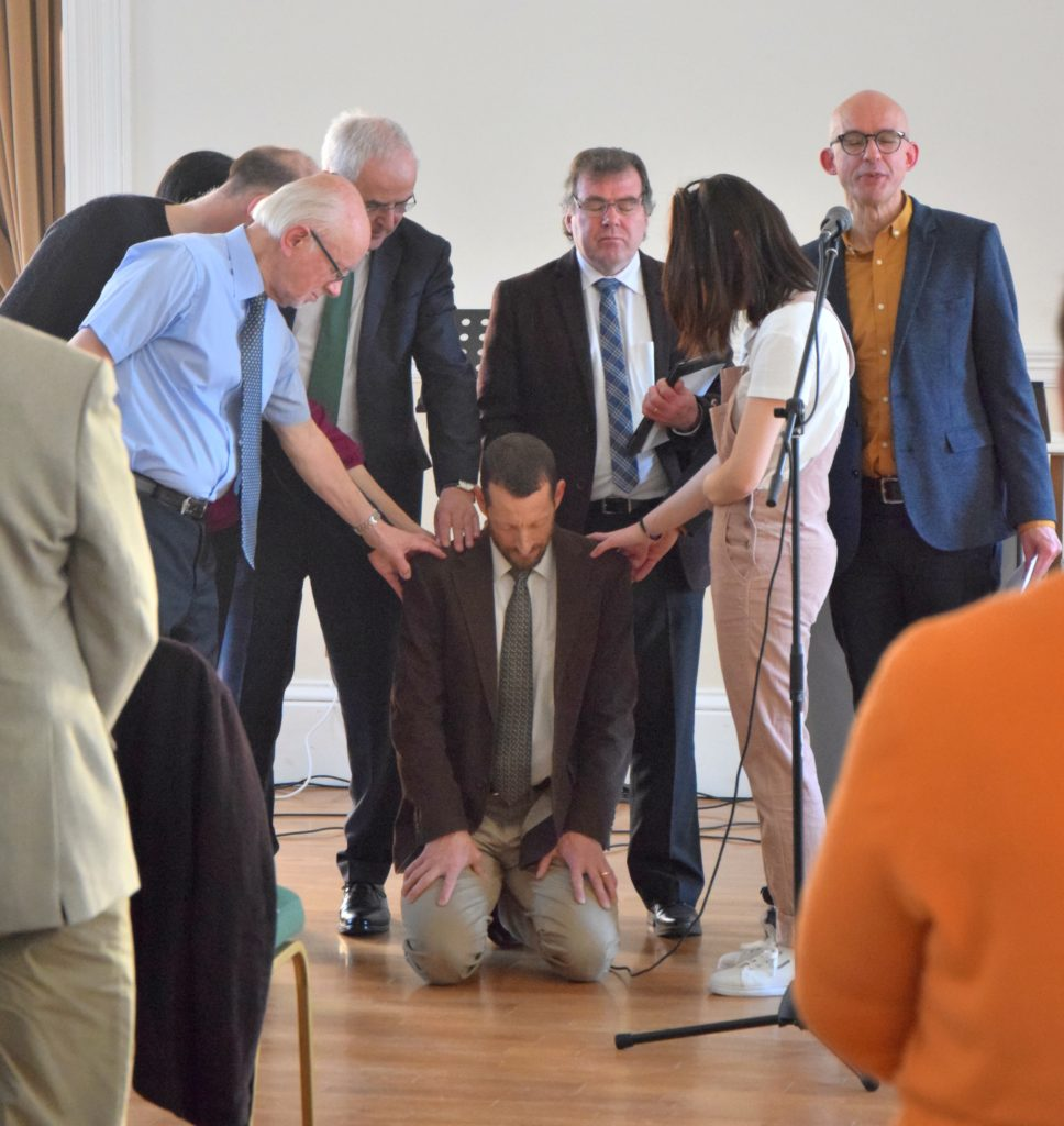 Members of the congregation and other churches lay hands on Rev Jasper.