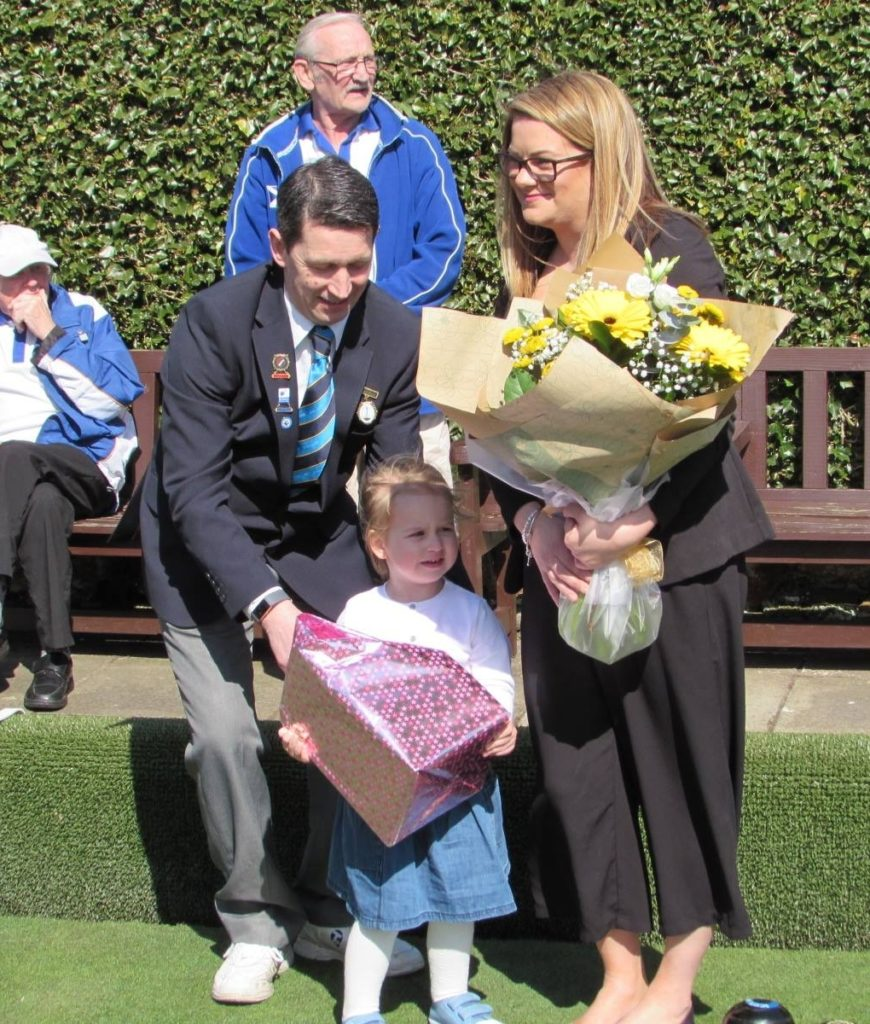 Vice president David Brown helps his daughter, Olivia, present Lorraine Dalziel with a bouquet of flowers.