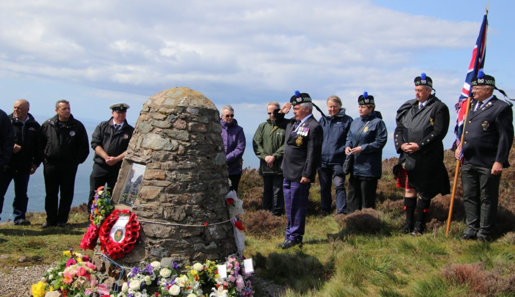George Rahman, chairman of the Royal British Legion Scotland's Campbeltown branch salutes before the cairn.