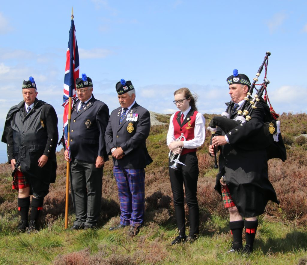 Piper John McGeachy performs at the service beside the cairn.