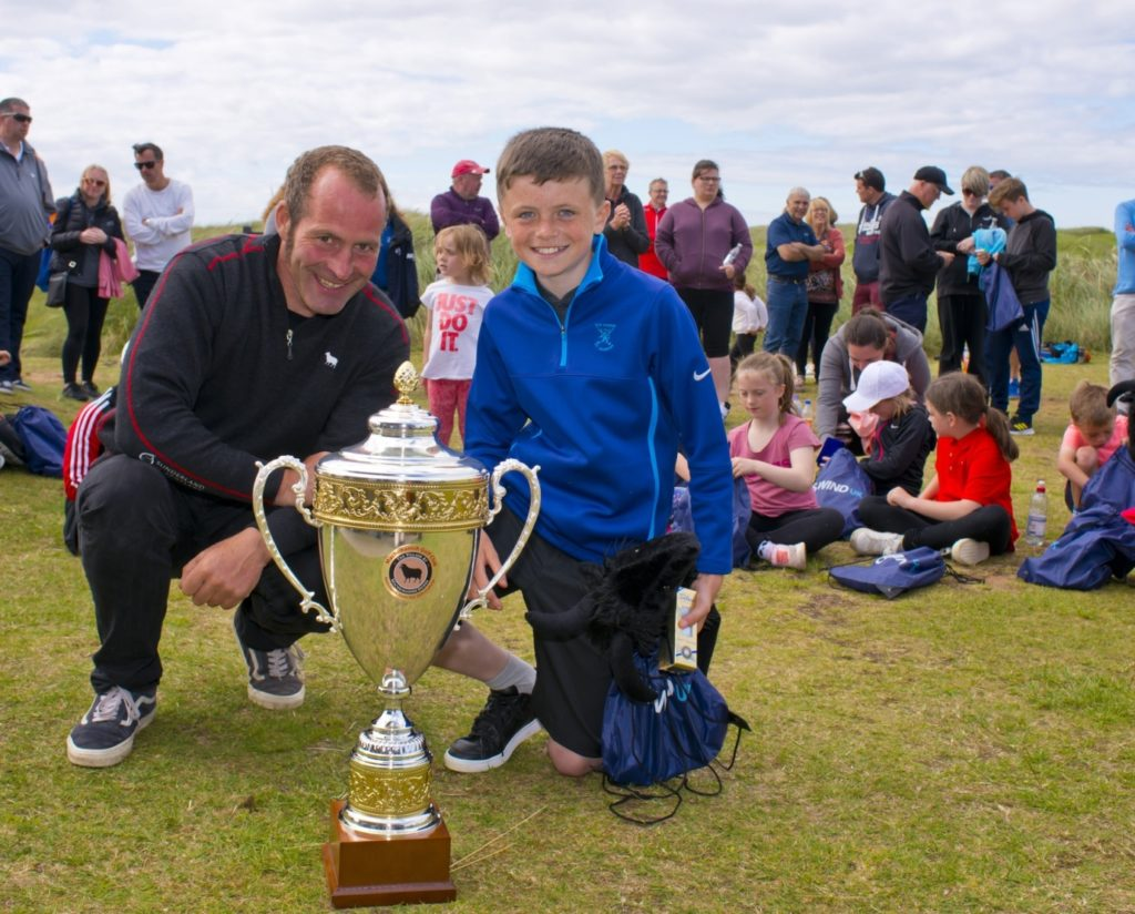 All the juniors who competed in the skills challenge were winners and received commemorative medals and goodie bags made up by the club's friends at CS Wind. Overall champions in four age divisions were awarded extra prizes. Jake MacMillan, pictured here with greenkeeper Simon Freeman, was the winner of the 10 to 12-year-old section. Photo: John McFadyen.