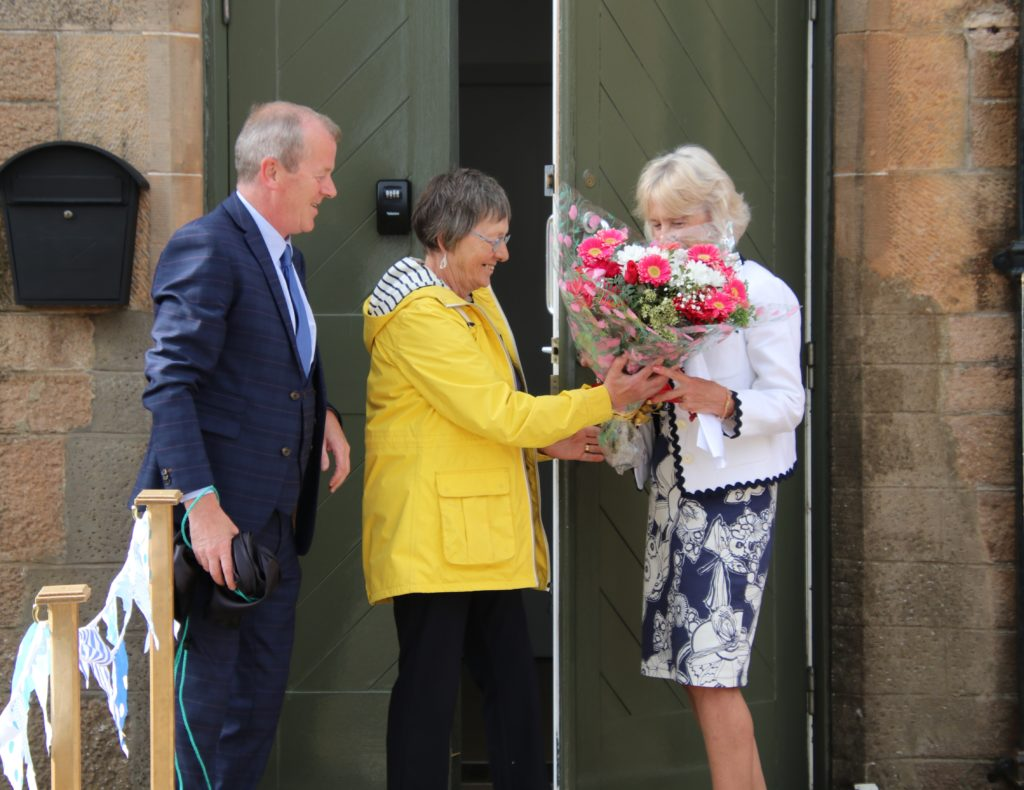 Felicity Kelly presents Anne Cousin with a bouquet of flowers.