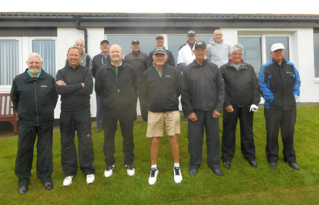 The group, dressed for the weather, before teeing off.