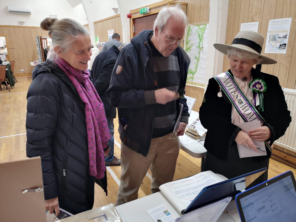 Christine Ritchie, dressed as a suffragette, explaining some of the heritage items on display to visitors.
